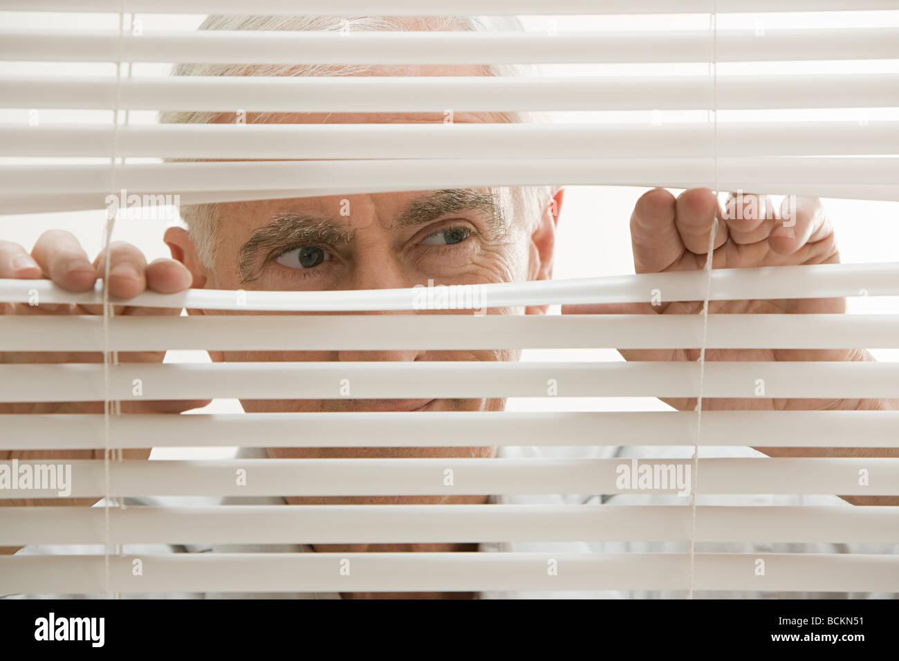 Mann auf der Suche durch Jalousien Stockbild