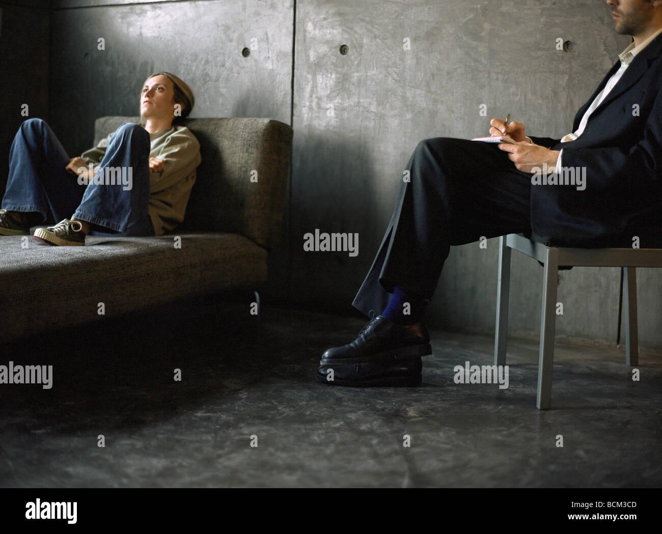 junge frau liegend auf der couch und therapeut sitzen im stuhl in der n he notizen stockfoto. Black Bedroom Furniture Sets. Home Design Ideas