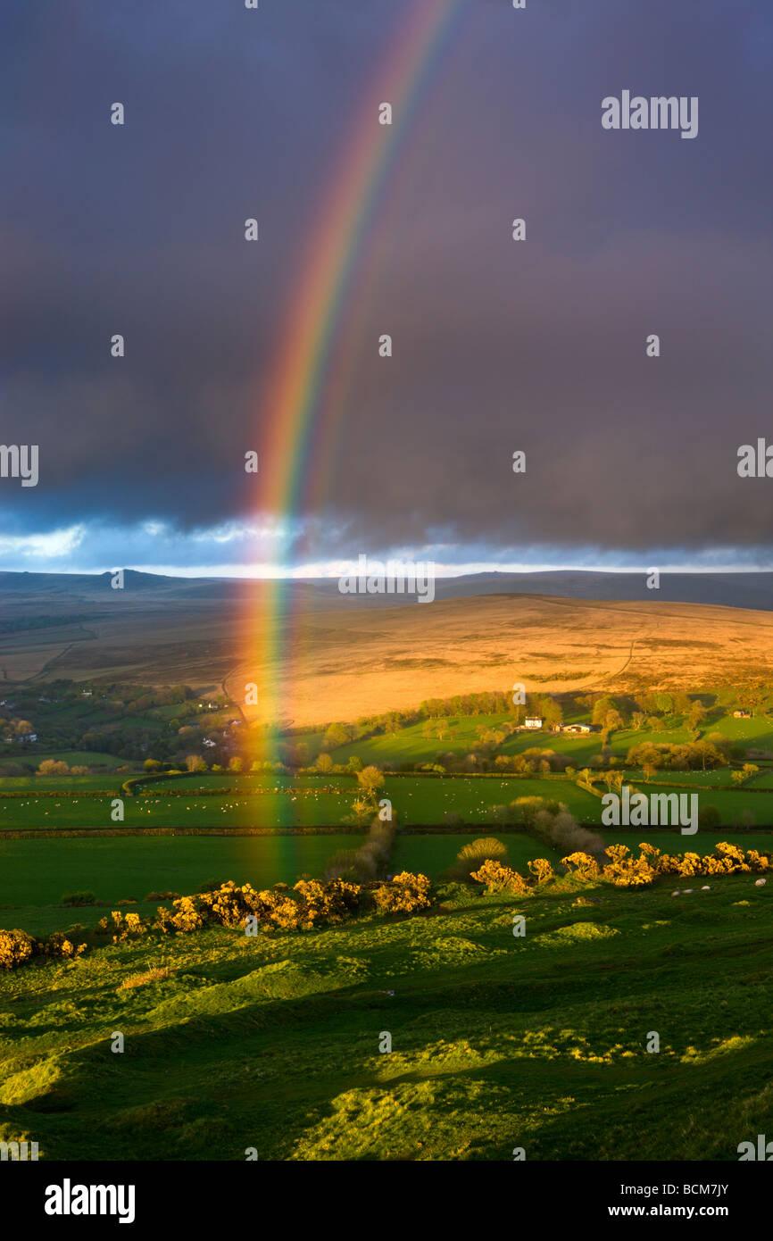 Regenbogen über dem hügeligem Ackerland an den Rändern des Dartmoor National Park Devon England Frühjahr Stockbild