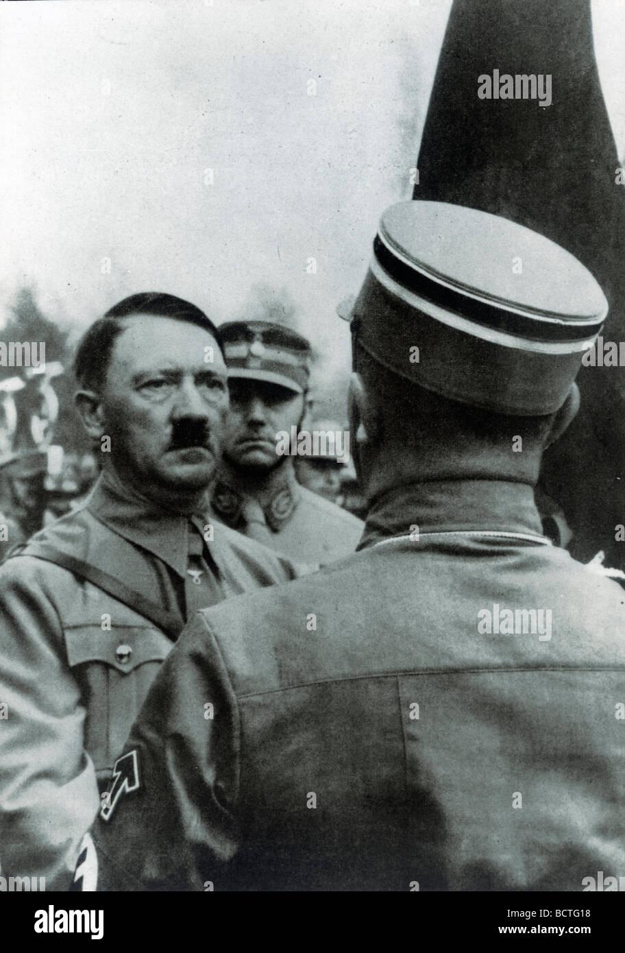 """Adolf Hitler """"weihen"""" neue Fahnen mit der Blutfahne Blut Flagge hinter ihm Stabschef Viktor Lutze, historisches Stockbild"""