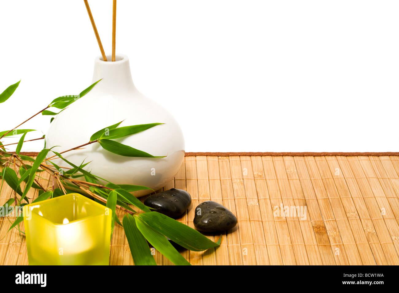 Spa und Wellness Stillleben mit Bambus-Zweig, Kerze, Steinen, Vase mit Räucherstäbchen, Ausschnitt Stockbild