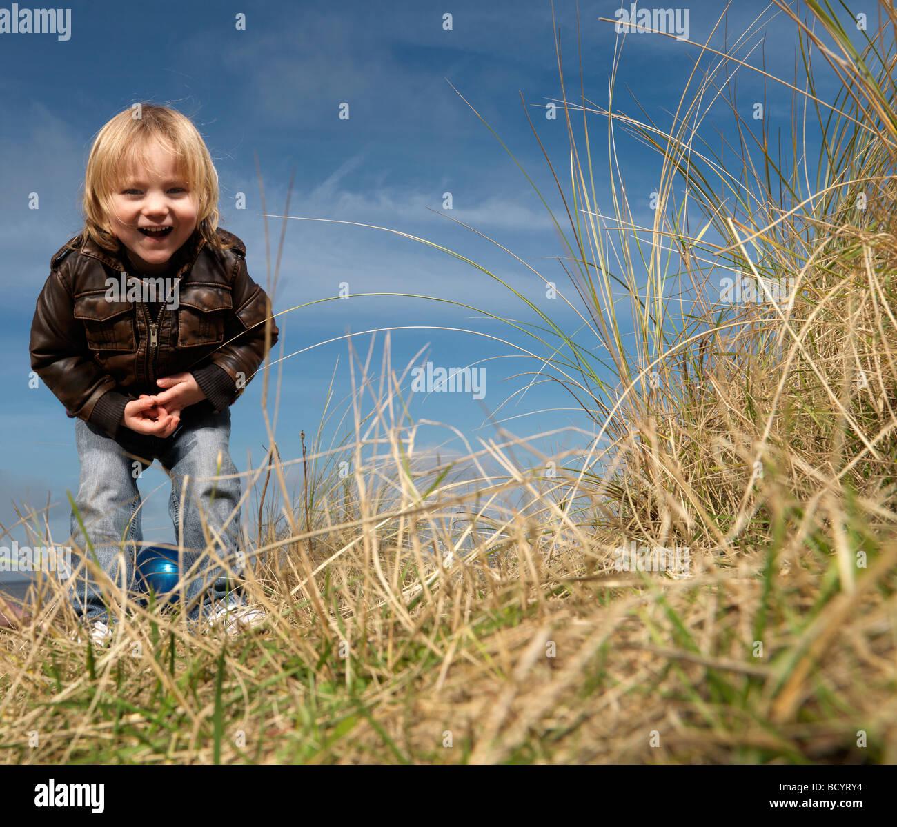 Junge am Strand spielen mit ball Stockbild
