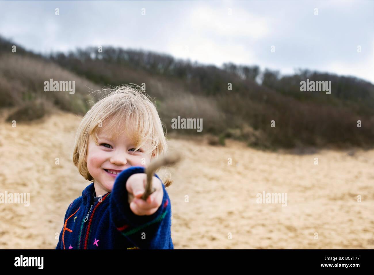 Boy am Strand zeigen mit stick Stockbild