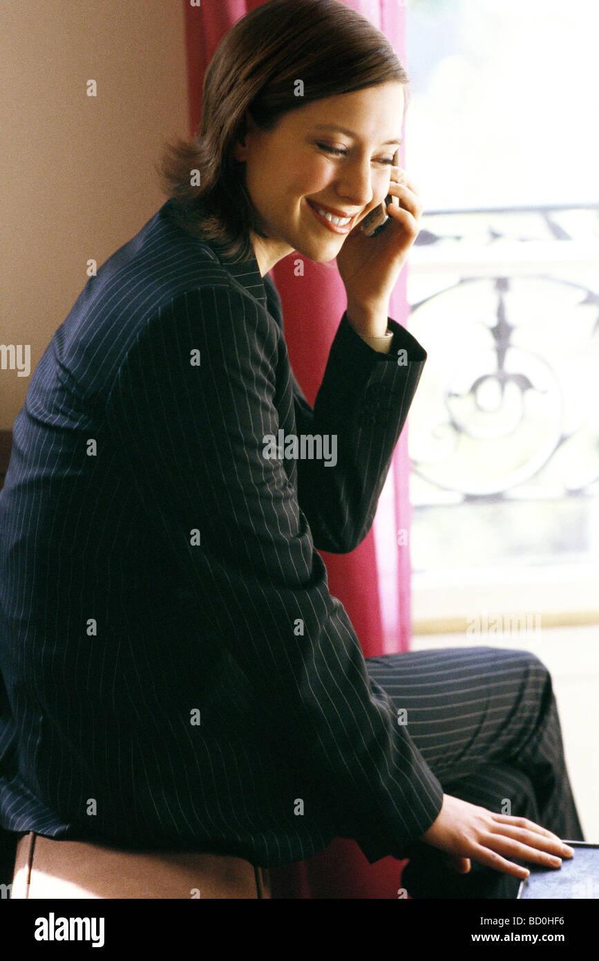 Frau in voller Fenster mit Handy sitzen Stockbild