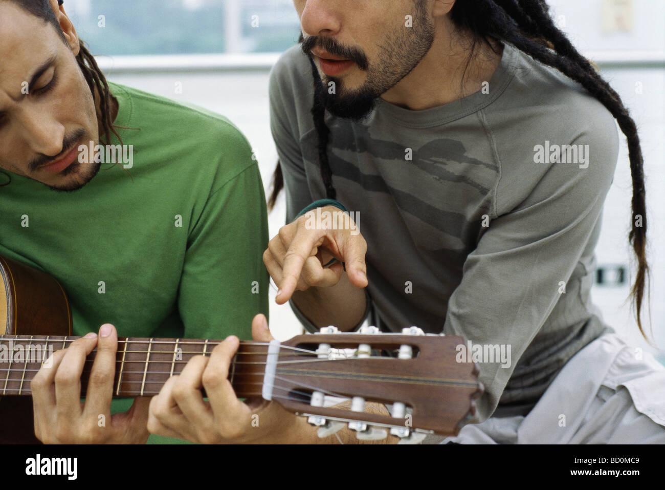 Man lehrt Freund, Akustik-Gitarre zu spielen Stockbild
