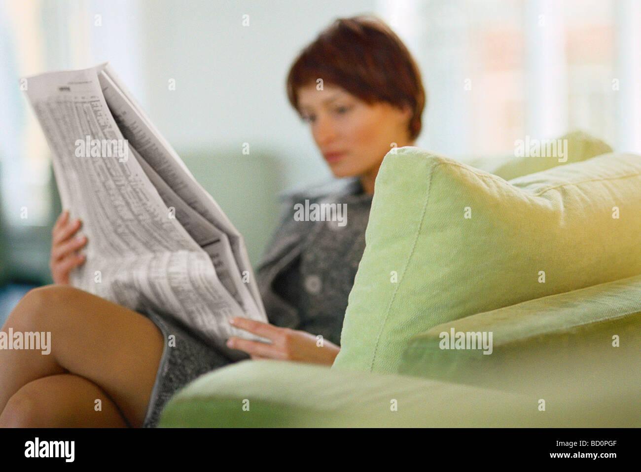 Geschäftsfrau auf Sofa lesen Zeitung Stockbild