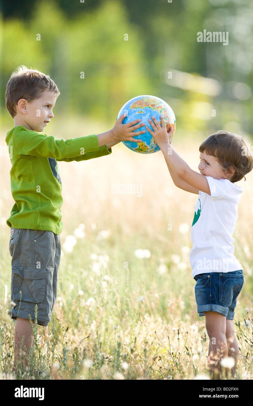 Kinder spielen mit Globus auf Wiese Stockbild