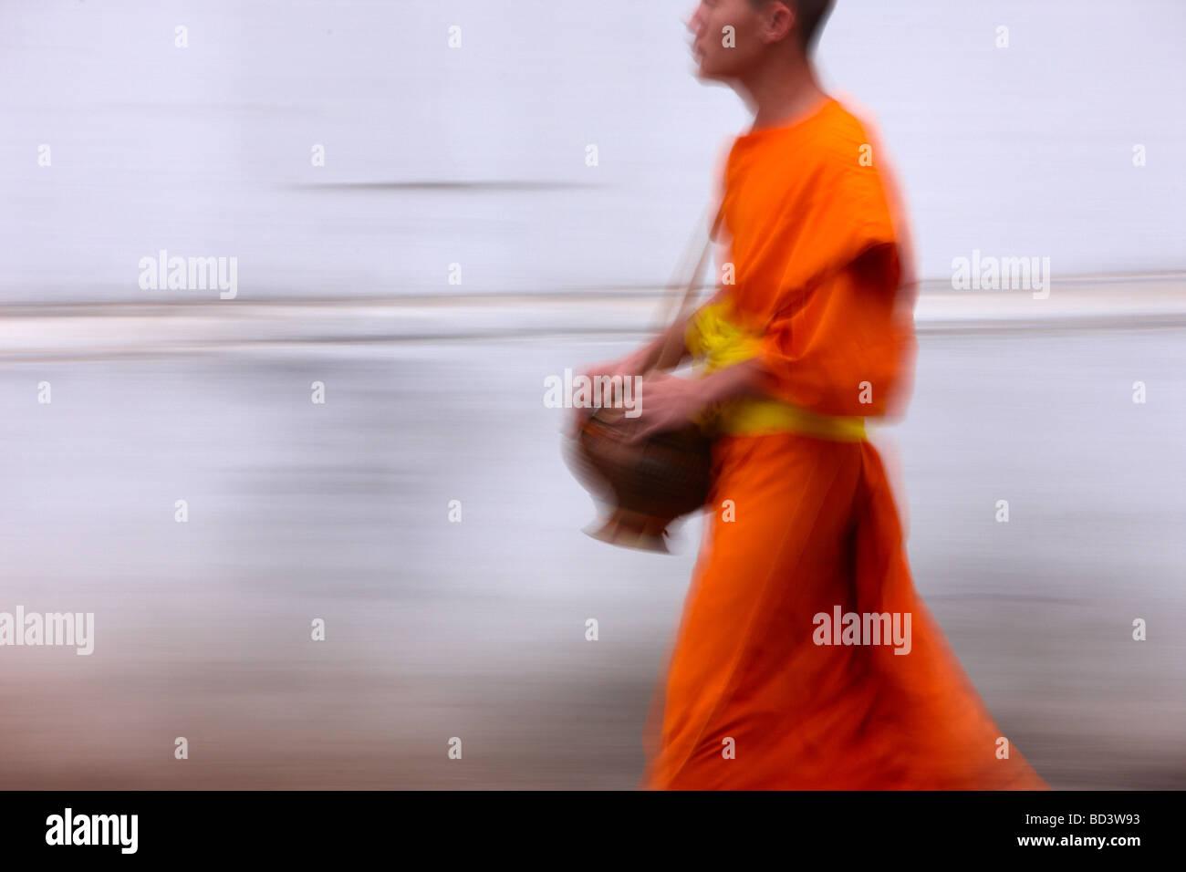 Mönche ein Spaziergang durch die Straßen in der Morgendämmerung sammeln Geschenke von Lebensmitteln, Stockbild