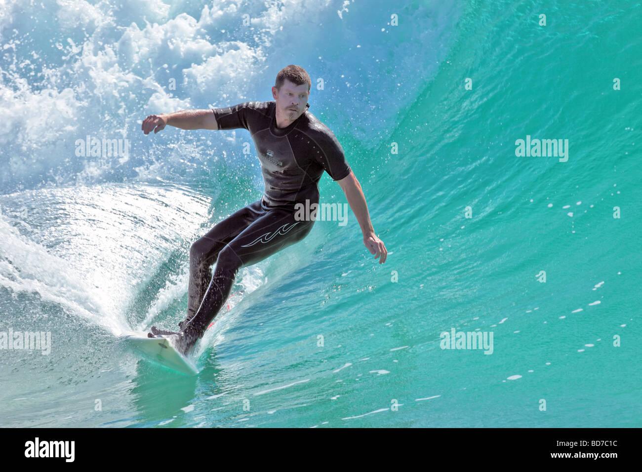 Surfer fängt eine Welle für eine Fahrt ins Ufer am späten Nachmittag Stockbild