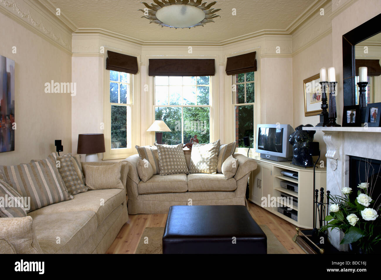 beige sofas in creme wohnzimmer mit schwarzen vorh ngen auf erker und fernsehen am regal neben