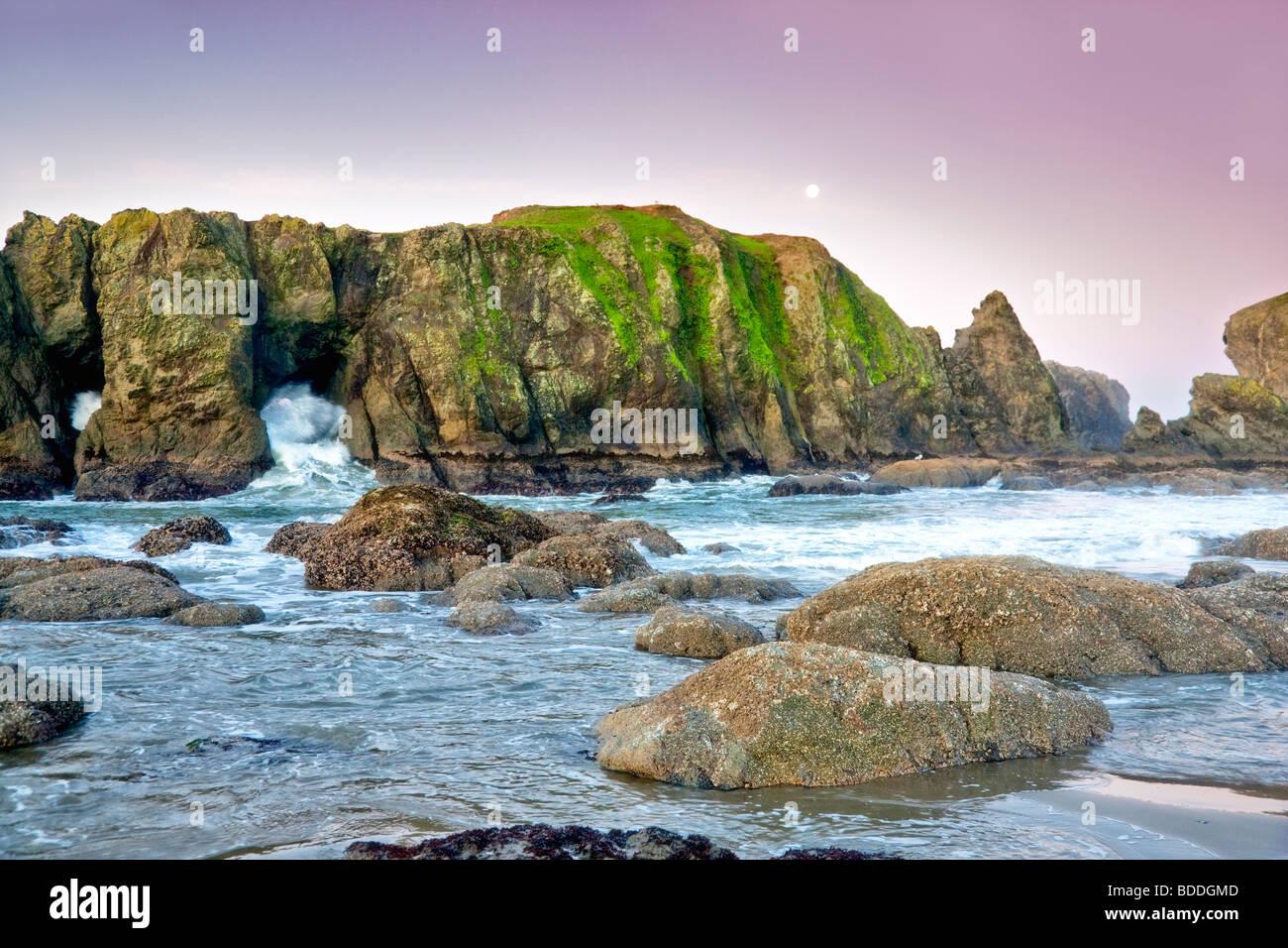 Felsen, Mond, Ebbe und Welle am Strand von Bandon. Oregon Stockbild