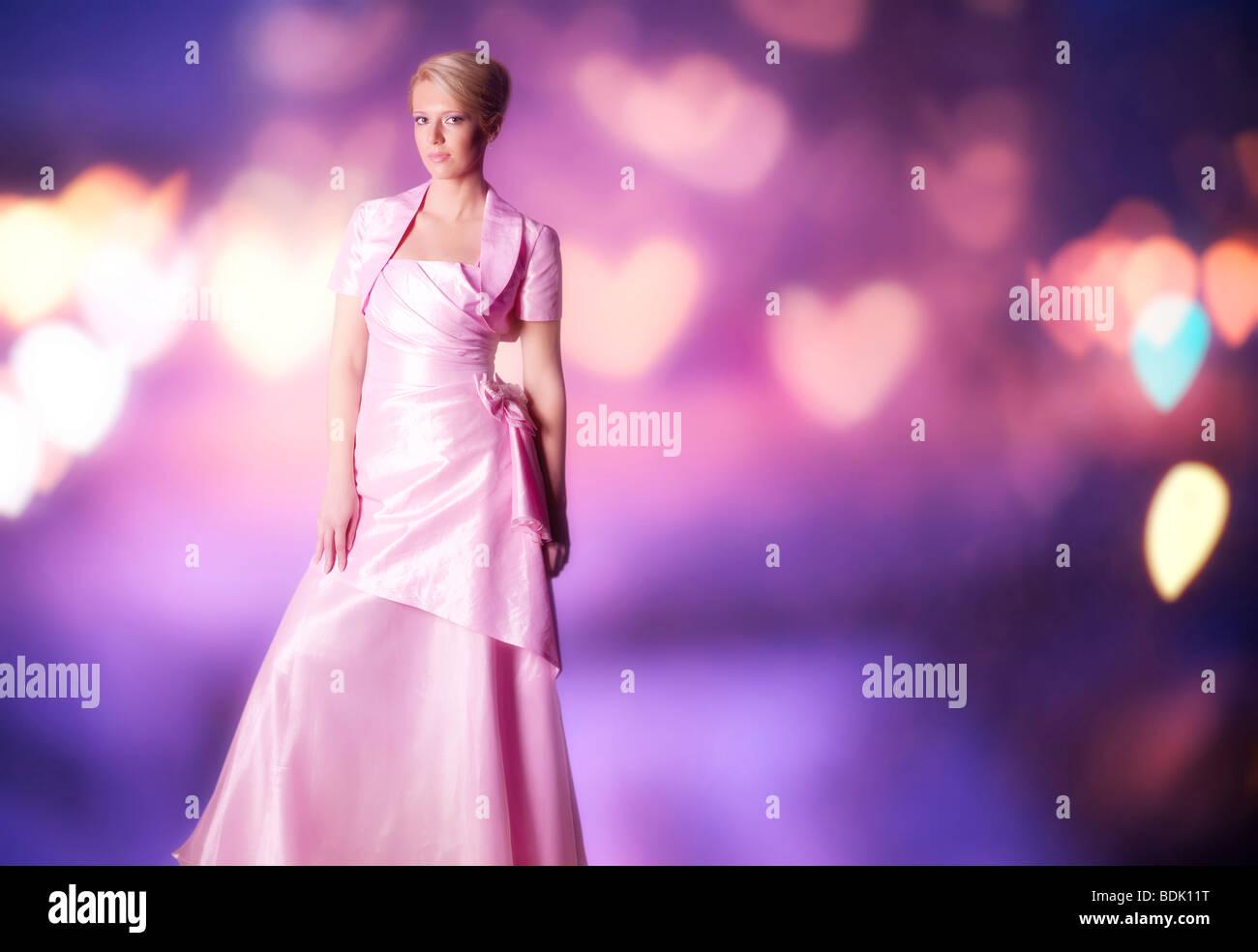 Frau in rosa Kleid auf abstrakte unscharfen Hintergrund. Stockbild