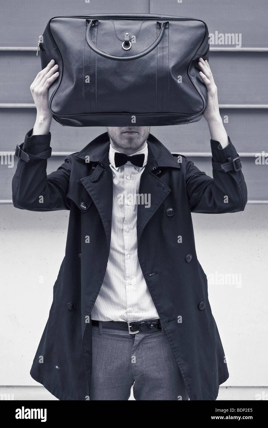 Ein junger Mann trägt eine Fliege und einen schwarzen Regenmantel hält eine schwarze Tasche direkt vor Stockbild