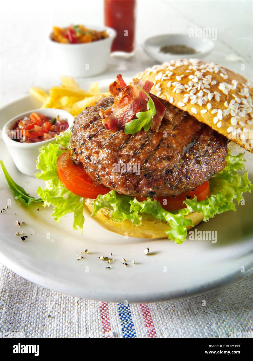 Char, gegrilltes Rindfleischburger und Speck mit Pommes Frites und Salat und ein Seseme Brötchen Stockbild