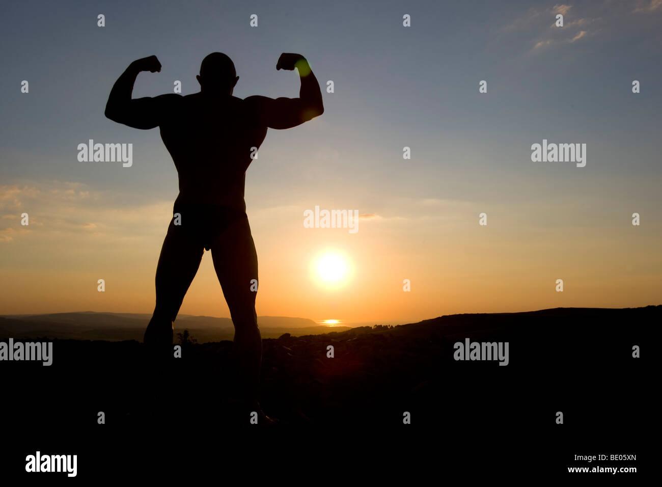 Bodybuilder stellt bei Sonnenuntergang. Stockbild