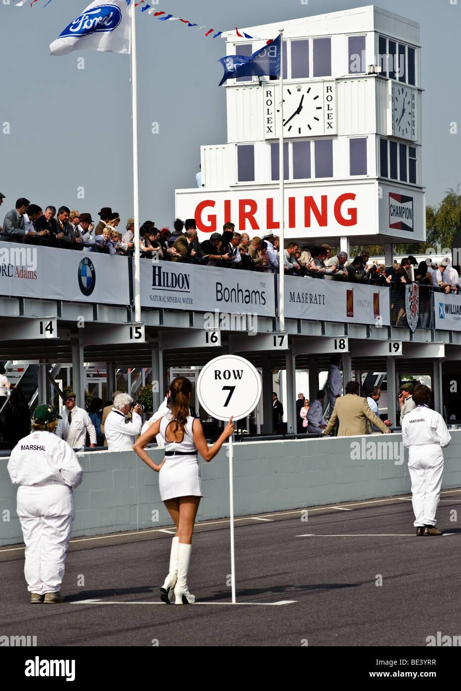 Ein Mädchen Kennzeichnung Rasterzeile 7 wartet auf die Autos in der Startaufstellung für den Start eines Stockbild