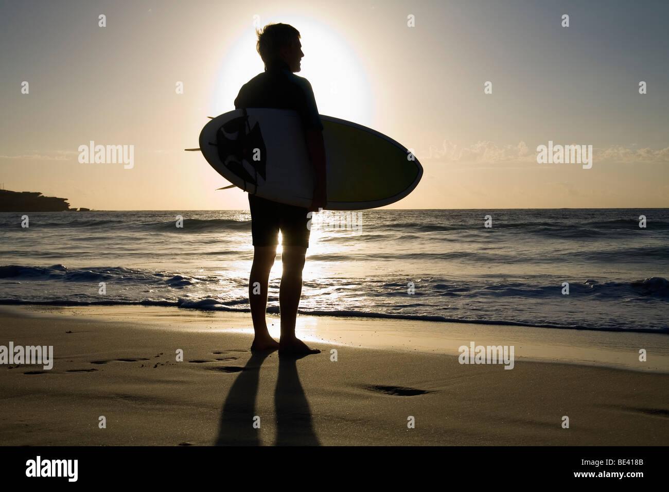 Eine Surfer mit Surfbrett wird von der Morgensonne Silhouette.  Bondi Beach. Sydney, New South Wales, Australien Stockbild