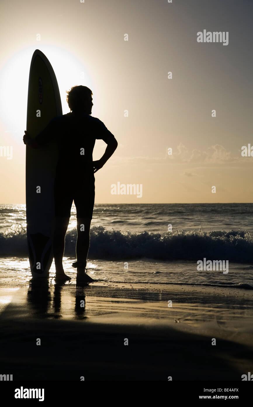 Eine Surfer schaut auf die Wellen am Bondi Beach. Sydney, New South Wales, Australien Stockbild