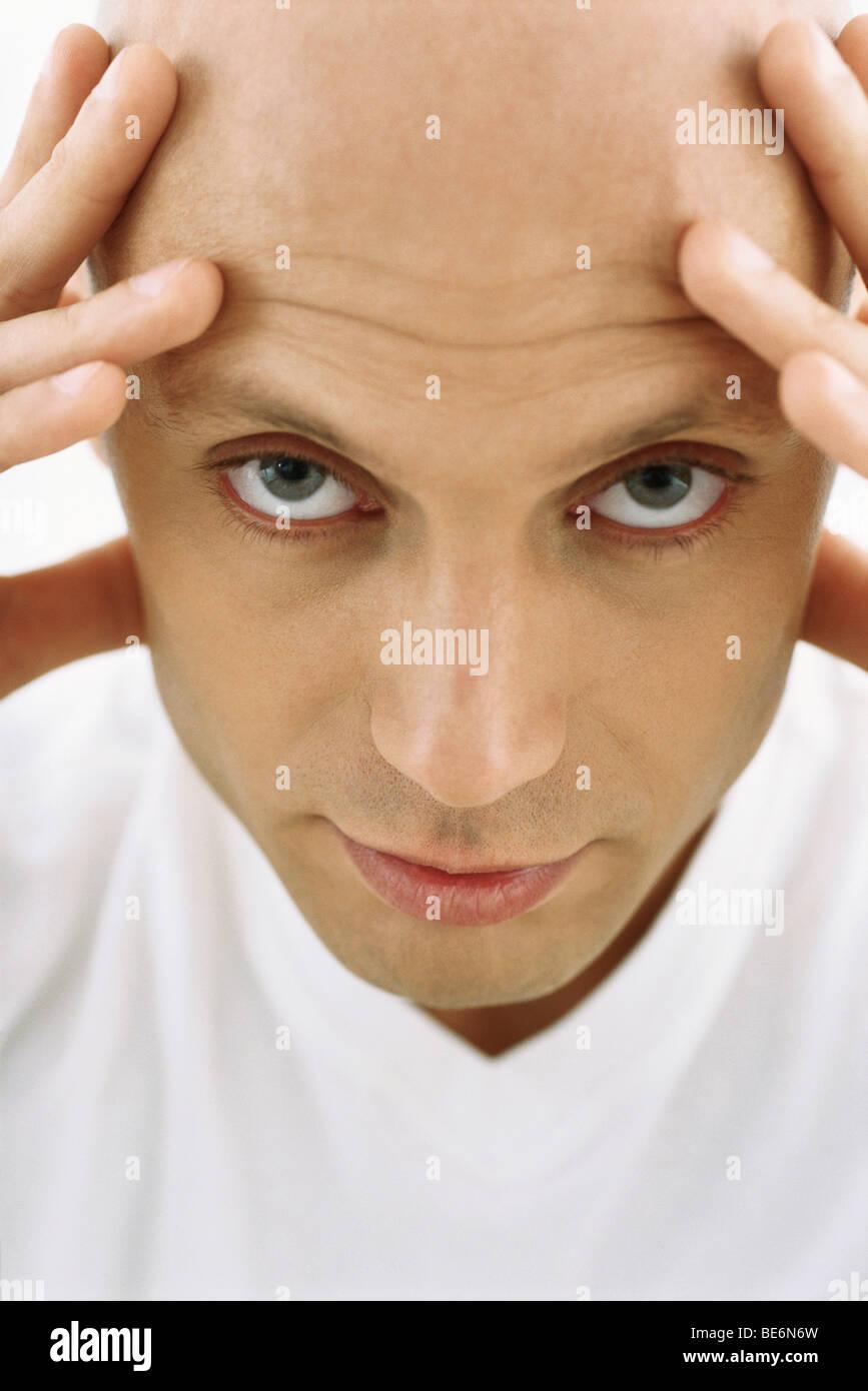 Glatzkopf Kopf haltend, Blick in die Kamera Stockbild