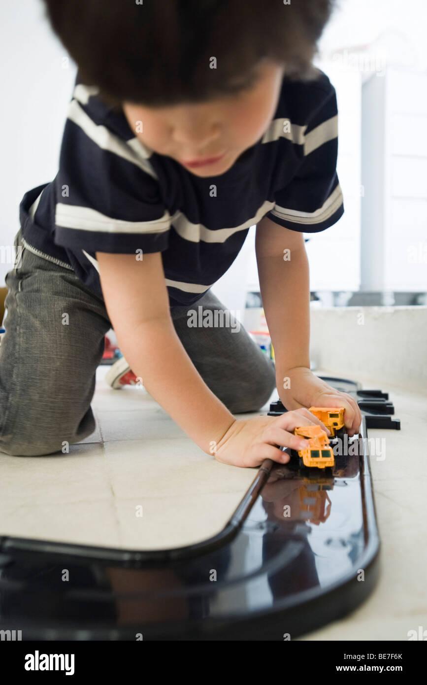 Kleiner Junge spielt mit Autos auf der Strecke aus Kunststoff Stockbild