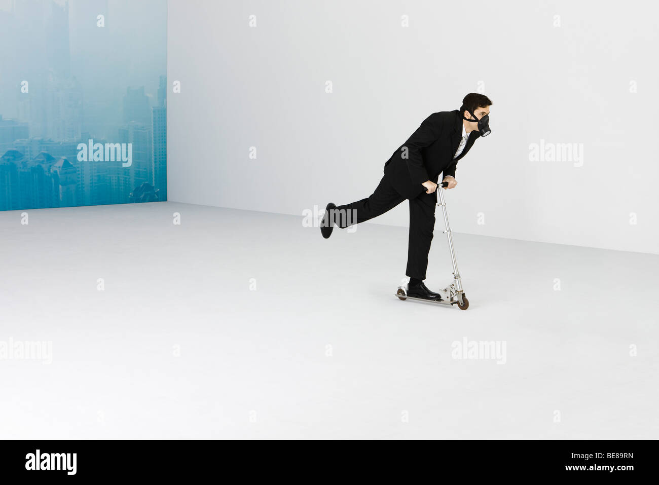 Geschäftsmann, tragen Gasmaske Reiten Push Scooter, Stadtbild von Smog im Hintergrund verdeckt Stockbild