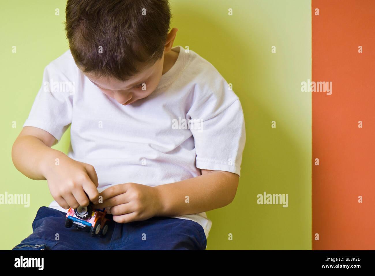 Kleiner Junge spielt mit Spielzeug-Auto Stockbild