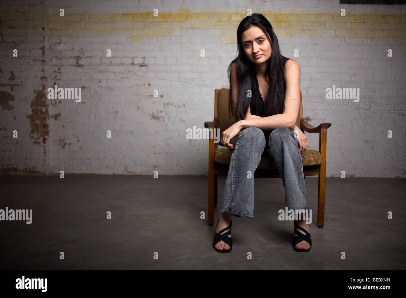 Eine hübsche Latein oder Spanisch Frau sitzt auf einem Stuhl in einem leeren Raum. Stockbild