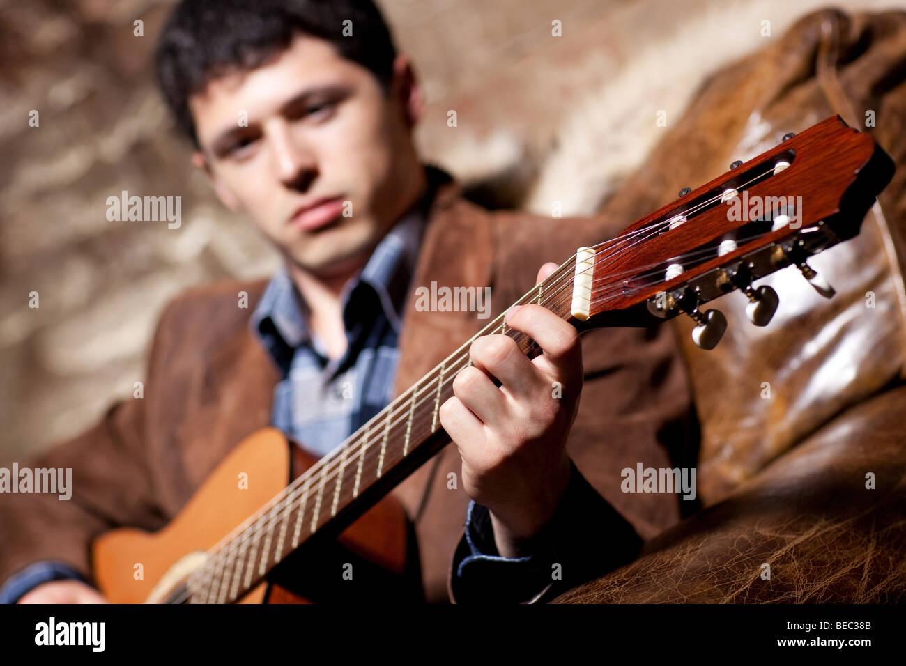 Junger Mann an der Gitarre in einem Sessel sitzend spielen. Auf Seite konzentrieren. Stockbild