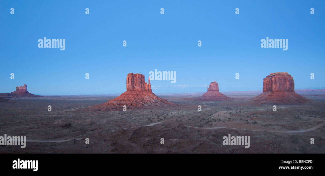 Monument Valley während des Sonnenaufgangs mit klaren blauen Himmel und roten Steinen. Stockbild