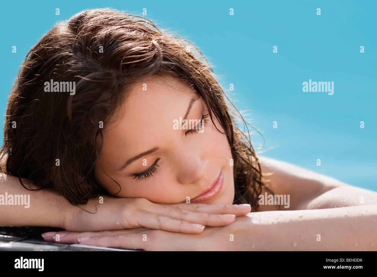 Nahaufnahme einer jungen Frau, die ein Nickerchen am Pool Stockbild