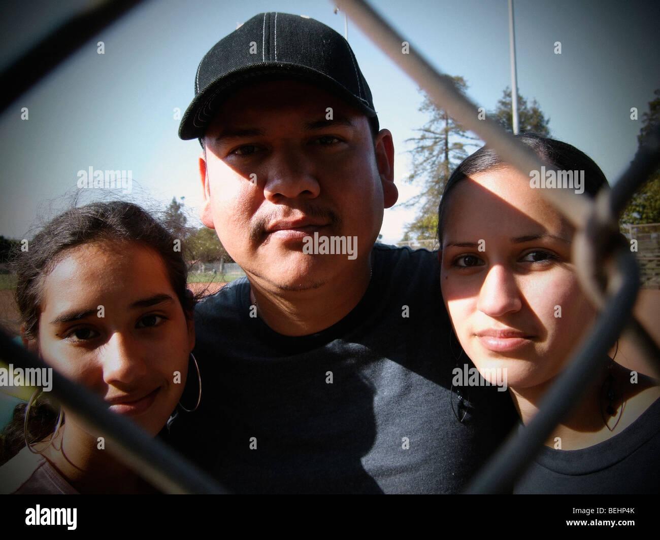 Vater mit zwei Töchtern Blick durch Baseball Zaun Stockbild