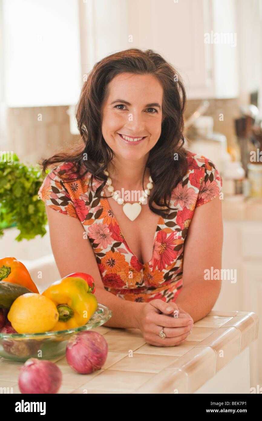 Porträt einer Mitte erwachsenen Frau stützte sich auf eine Küchentheke und lächelnd Stockbild