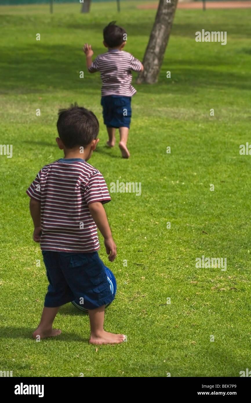 Zwei Jungs spielen Fußball in einem park Stockbild
