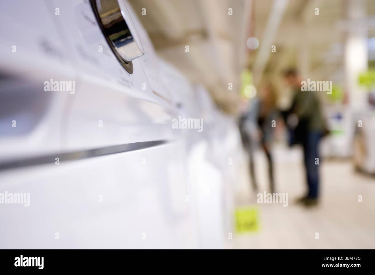 Drehknopf am Gerät, Shopper im Hintergrund Stockbild