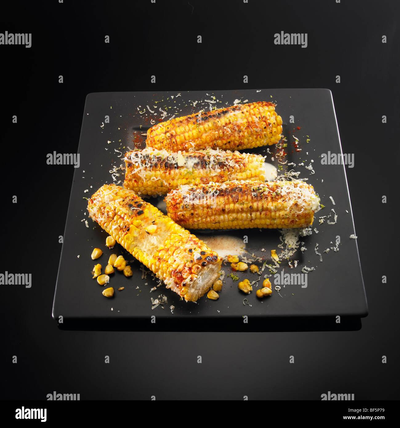 Gegrillte Maiskolben mit Butter, Käse und Chili, auf einem schwarzen Hintergrund. Stockbild