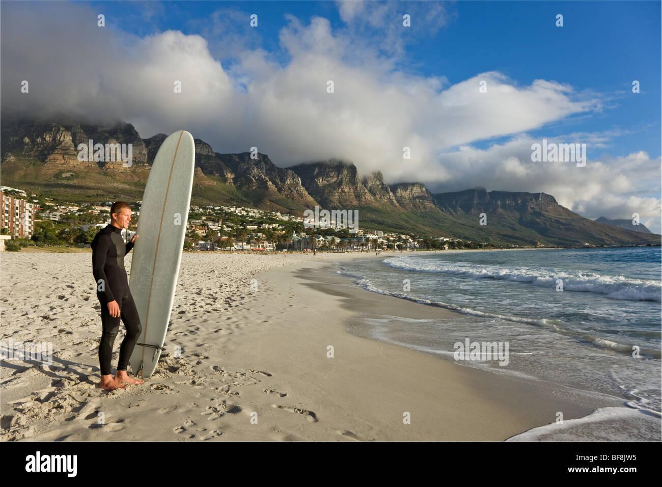 Surfer auf Camps bay Strand mit zwölf Apostel auf den Tafelberg im Hintergrund. Kapstadt-Südafrika Stockbild