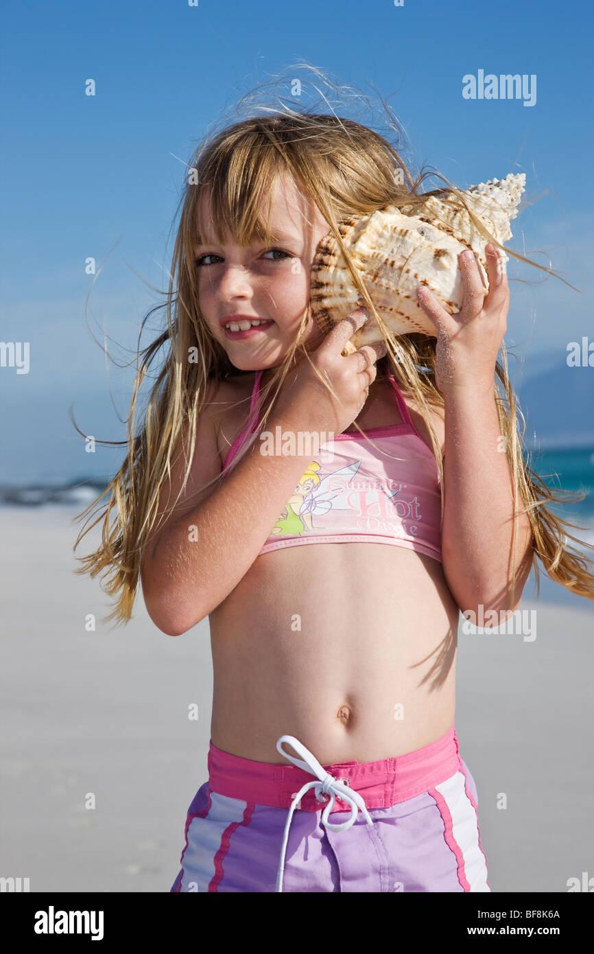 Niedliche kleine Mädchen halten Schale Ohr am Strand. Kapstadt-Südafrika Stockbild