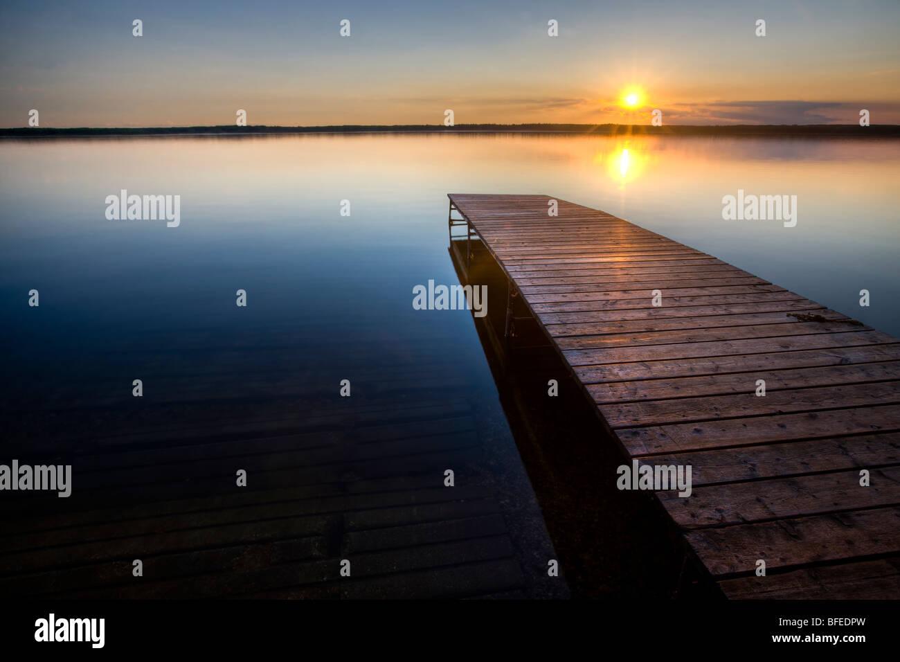 Sonnenuntergang über einem hölzernen Kai am Lake Audy, Riding Mountain National Park, Manitoba, Kanada Stockbild