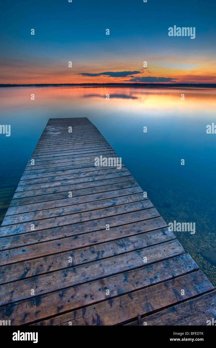 Sonnenuntergang über einem hölzernen Wharf am Lake Audy, Riding Mountain National Park, Manitoba, Kanada Stockbild