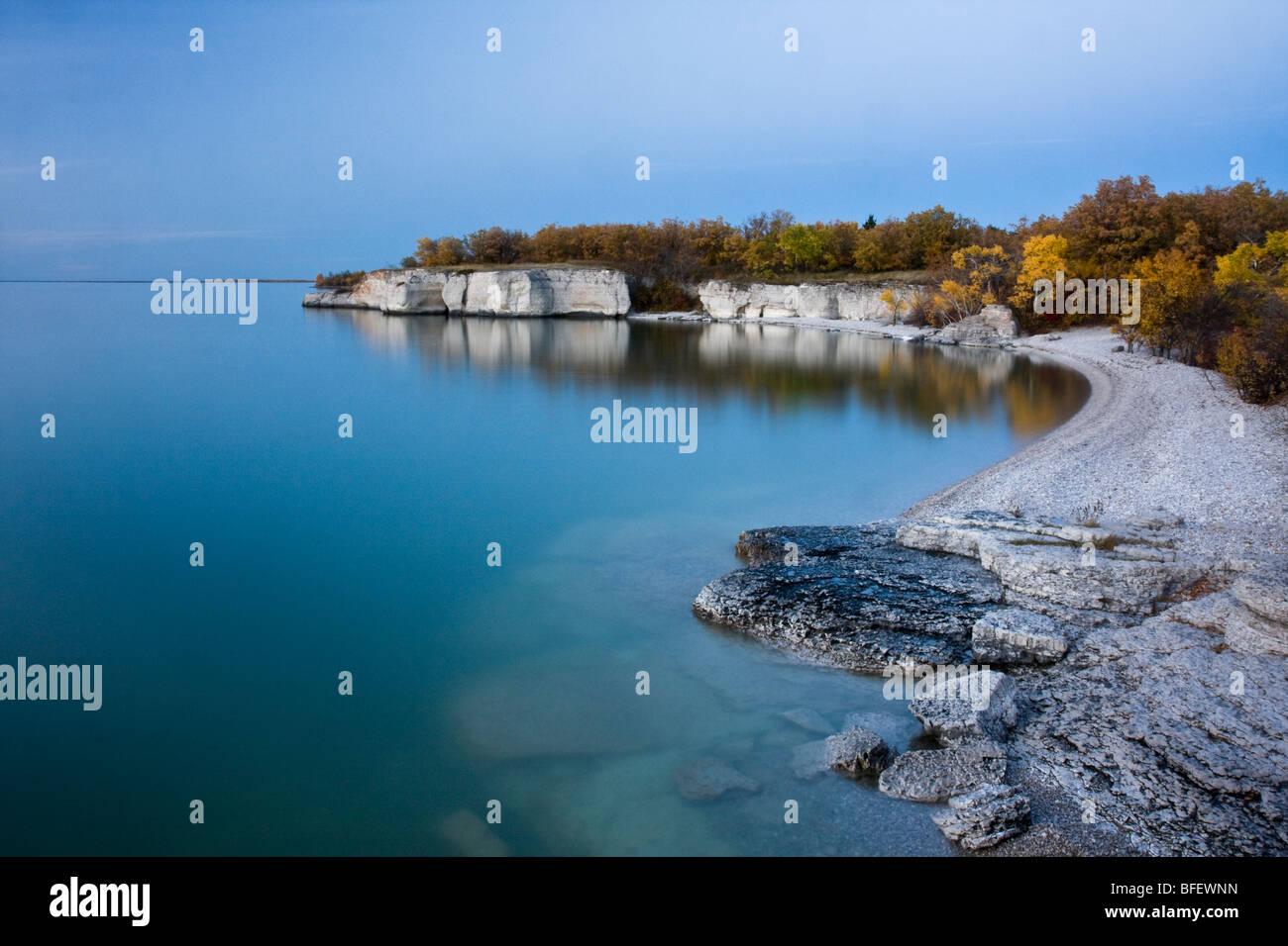 Reflexion von Klippen und Farben des Herbstes am Lake Manitoba bei Sonnenuntergang am steilen Felsen in Manitoba, Stockbild