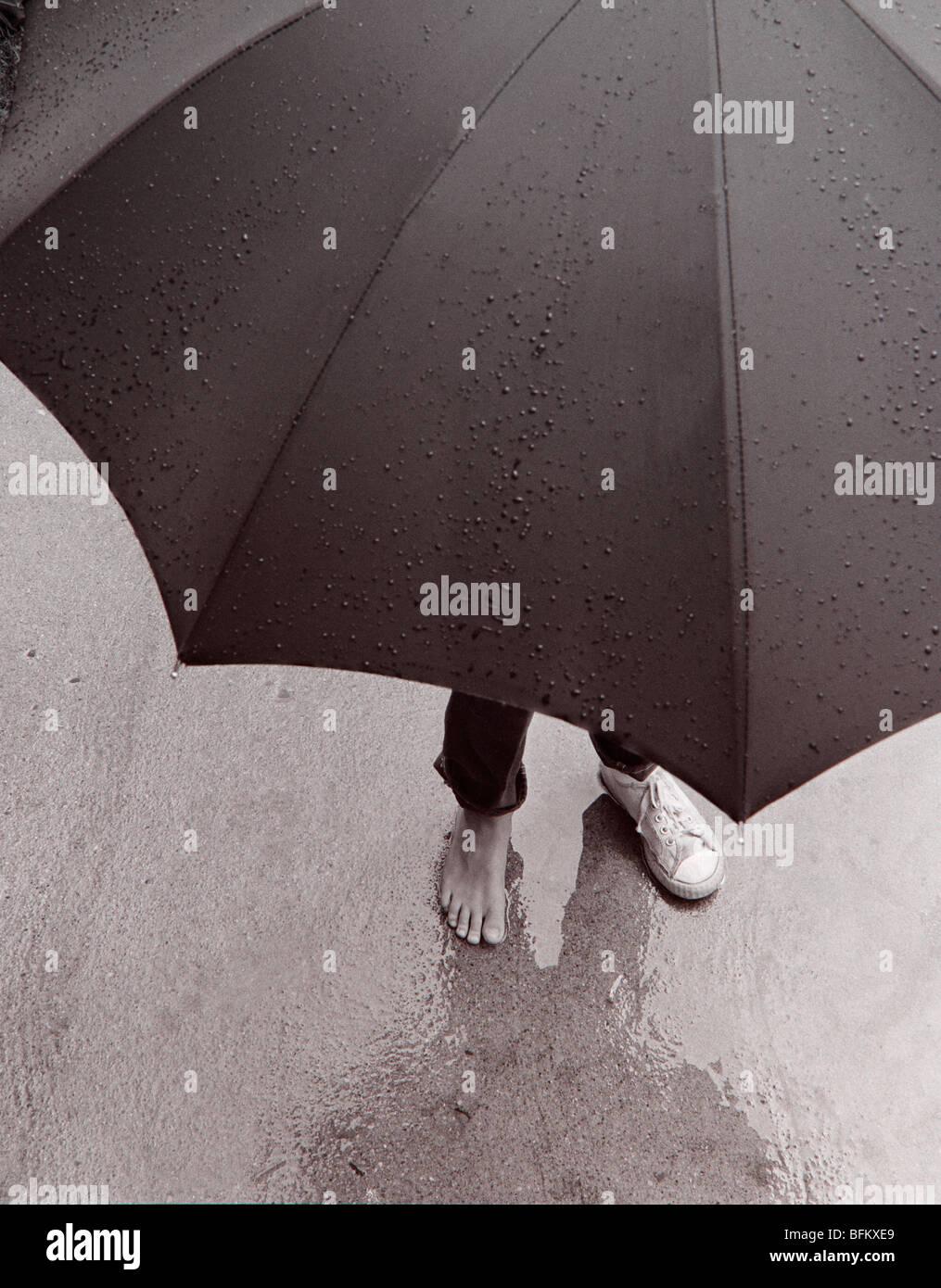 Person steht im Regen mit Regenschirm Stockbild