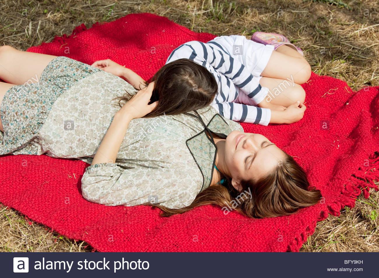 Mutter und Tochter liegen auf rote Decke Stockbild