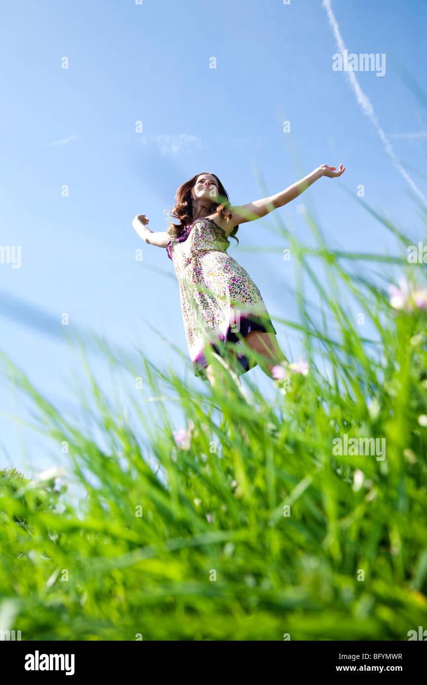junge Frau läuft durch Rasen im park Stockbild