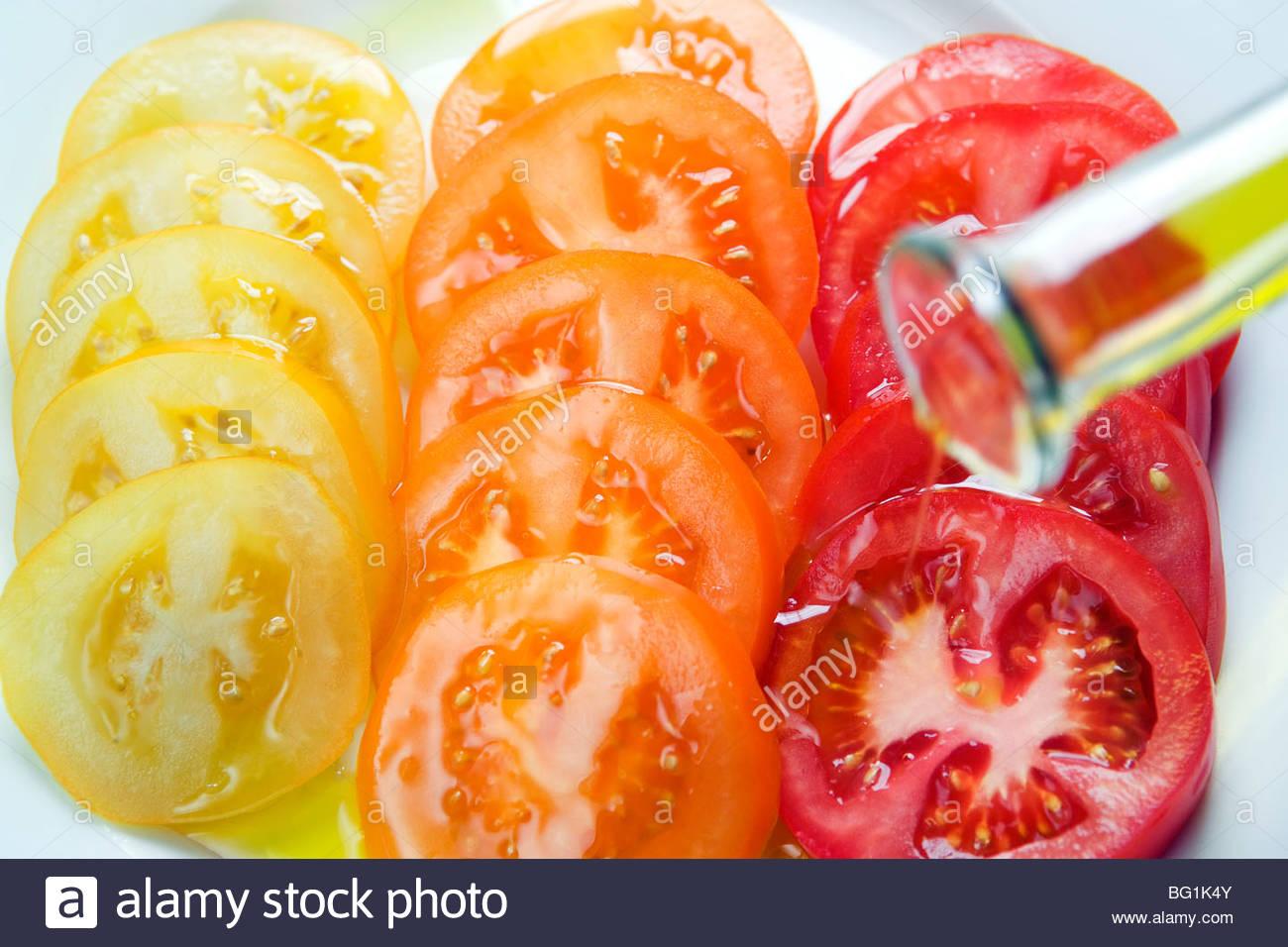Geschnittene Tomaten, gehackten Basilikum & beträufelt Olivenöl auf einem Teller Stockbild