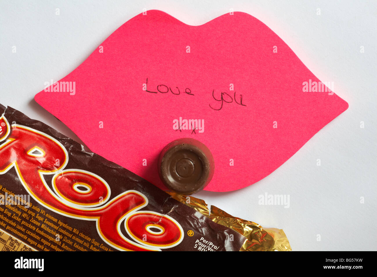 Liebe Dich - Die letzte Rolo - Liebe Sie xx auf rosa Lippen geschrieben Post it Note mit der letzten Rolo des Pakets Stockbild