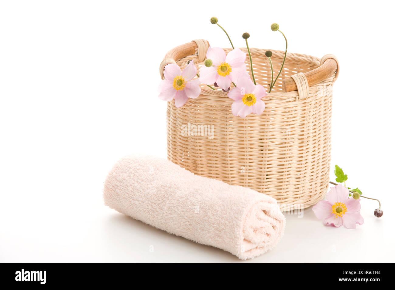 Geflochtenen Korb, gerollte Handtuch und Anemonen auf weißem Hintergrund Stockbild