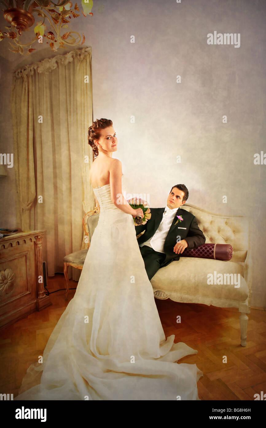 Voller Länge von Braut und Bräutigam in luxuriös und mit einem Vintage look innen mit Kleid von hinten gesehen Stockfoto