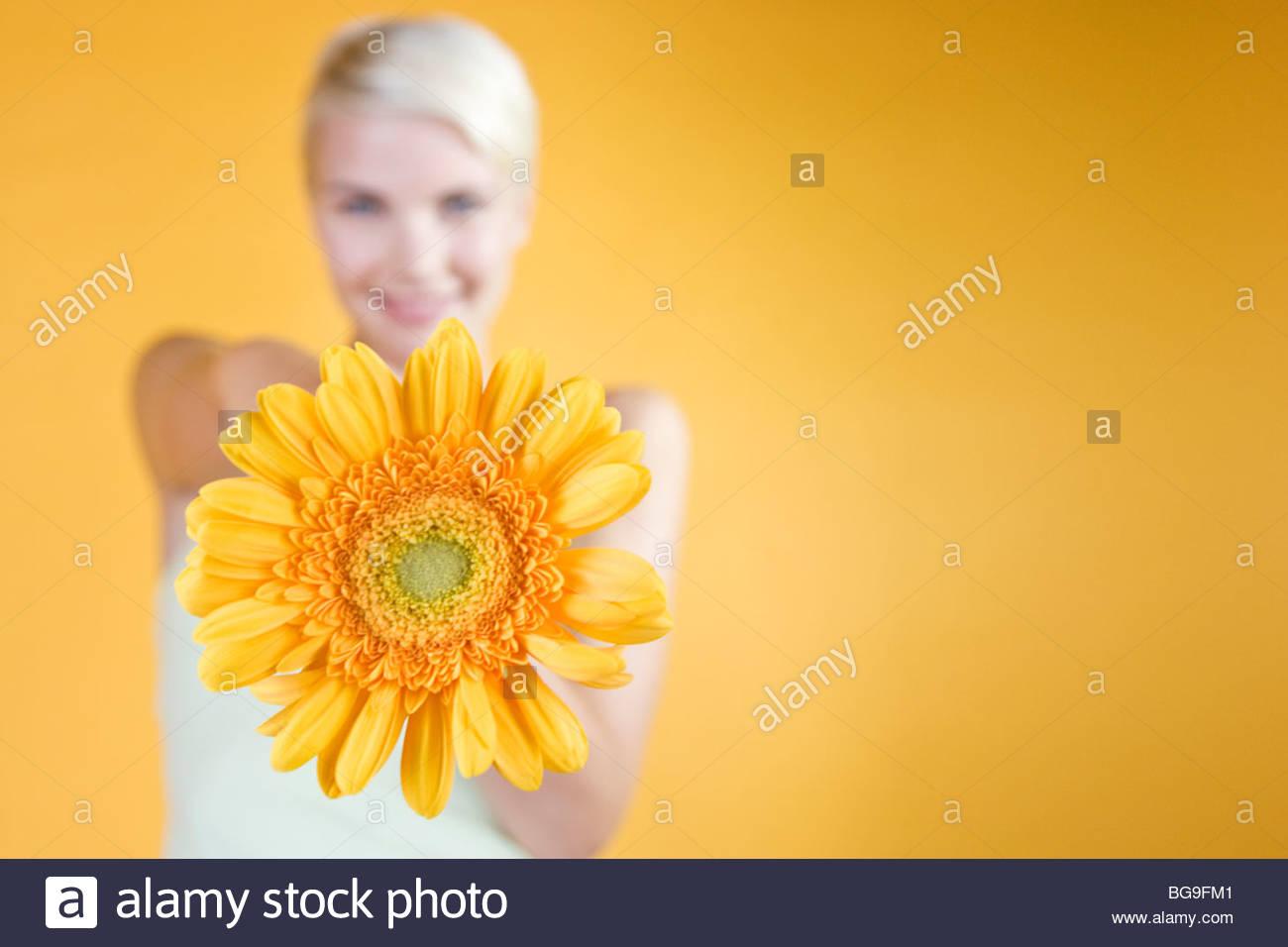 Eine junge Frau, die eine Orange Blume Stockbild