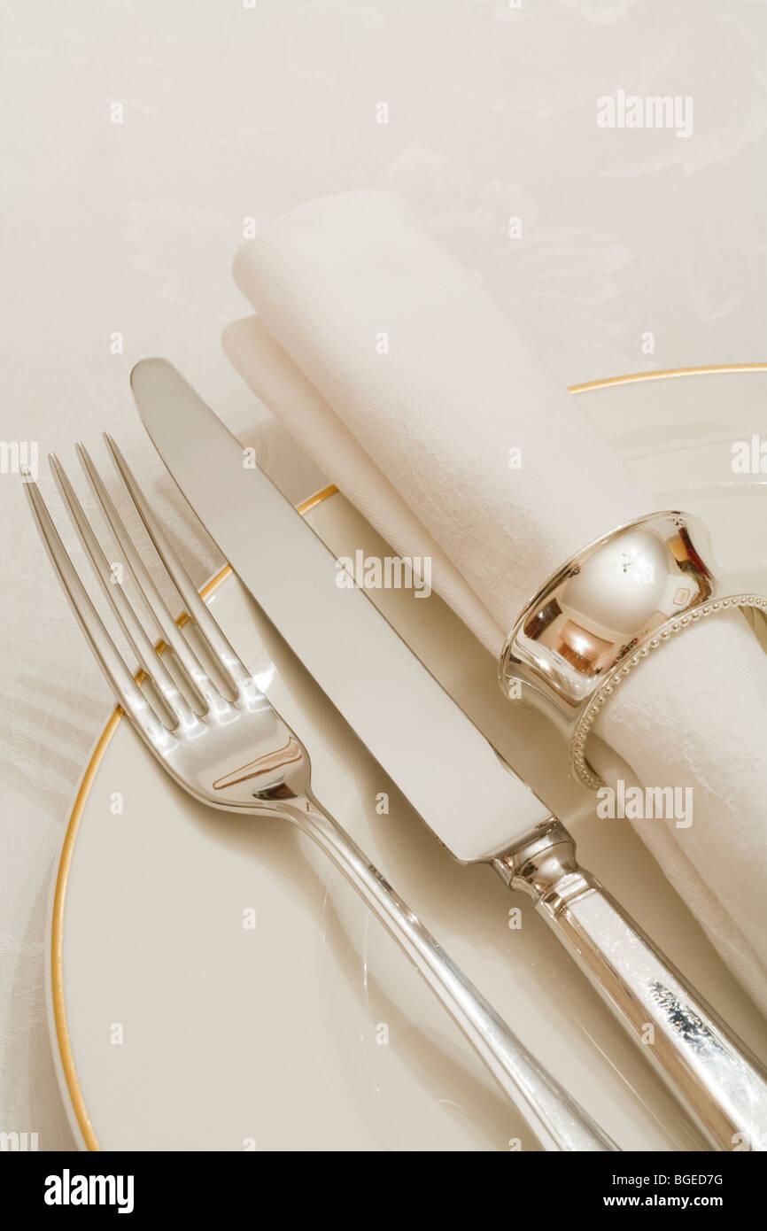 Gedeck mit Besteck, Teller und Serviette auf eine Damast Tischdecke Stockbild