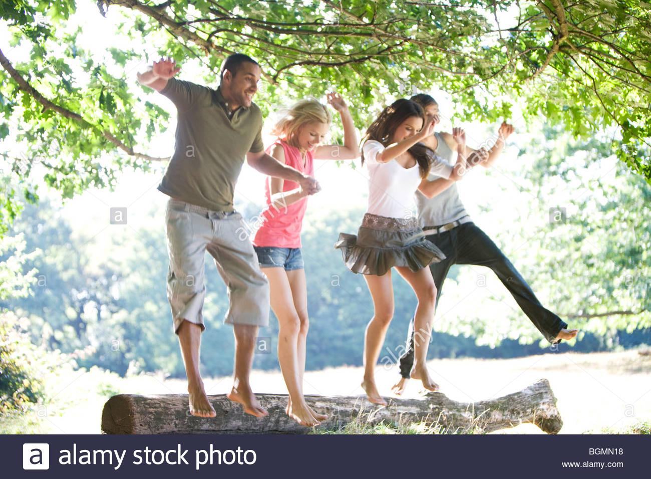 Vier junge Leute springen aus einem Protokoll Stockfoto